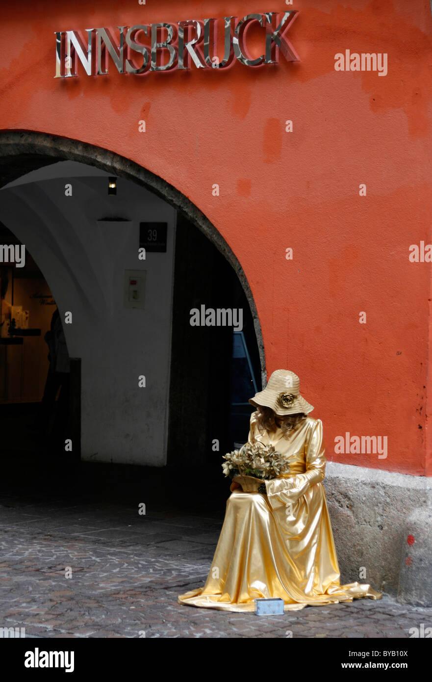 Mime street performer, gold dress, Herzog Friedrich Strasse, historic centre, Innsbruck, Tyrol, Austria, Europe - Stock Image
