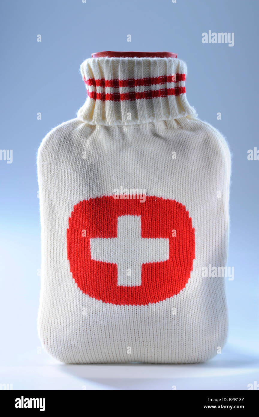 Hot water bottle with a red cross, first aid kit - Stock Image