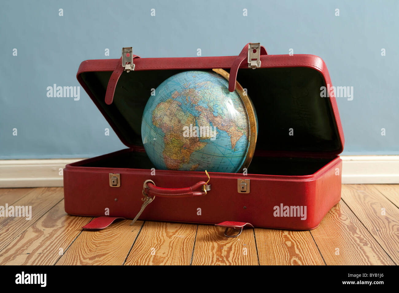 Globe in a suitcase, symbolic image for traveling, vacation, world trip - Stock Image