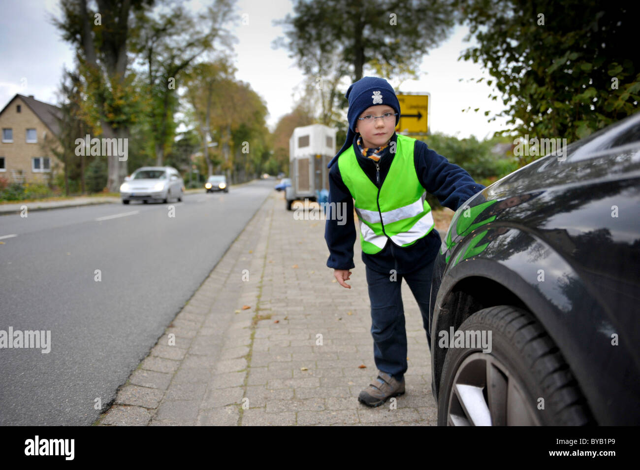 Little boy with reflective luminous vest is going to cross road Stock Photo