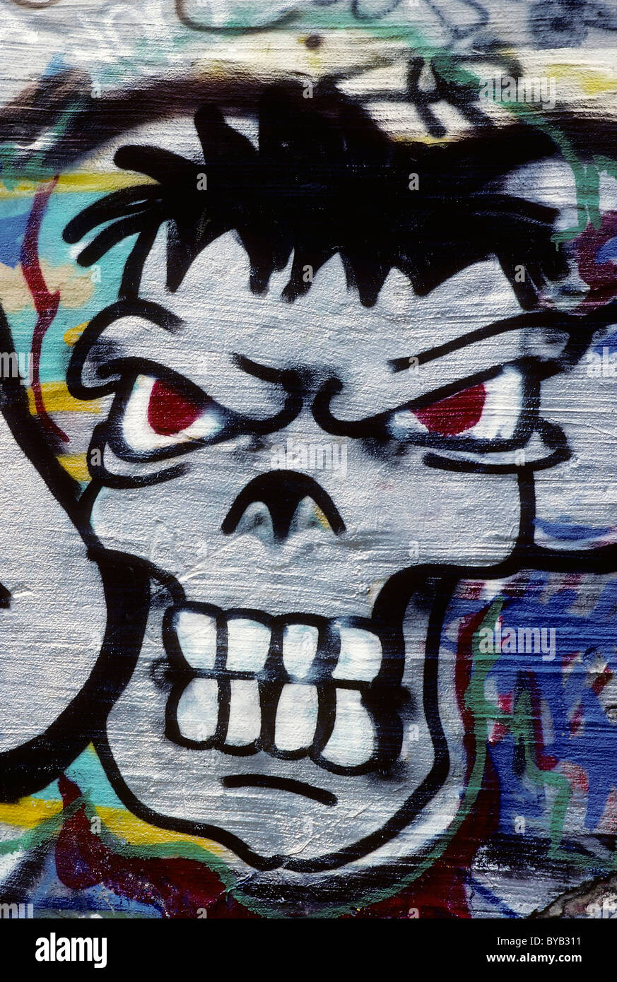 Grim face, looking aggressive with bared teeth, graffiti - Stock Image