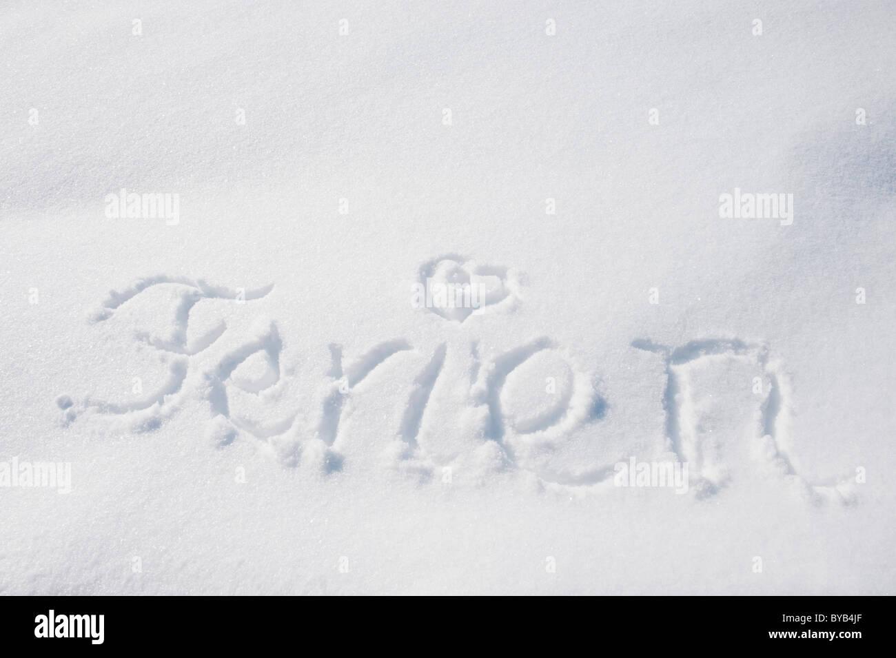 The word Ferien or holiday written in snow, winter, Landshut, Lower Bavaria, Bavaria, Germany, Europe - Stock Image