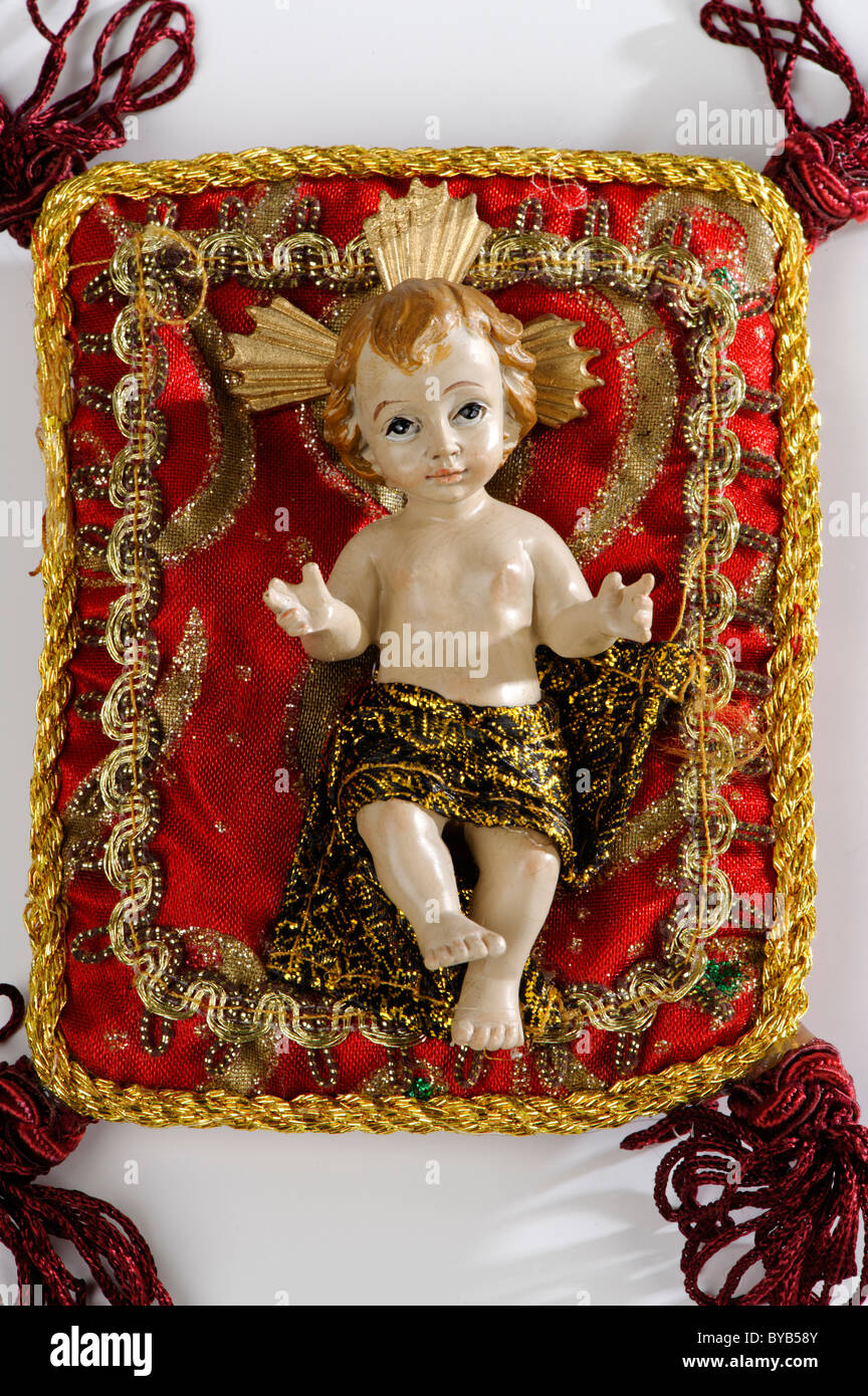 Baby Jesus figure on a embroidered cushion - Stock Image