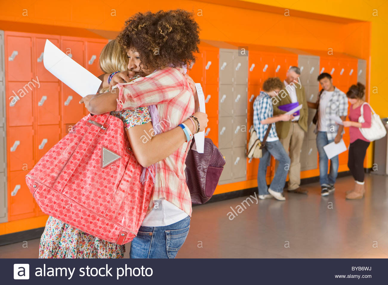 Excited students hugging after receiving good news about test results - Stock Image