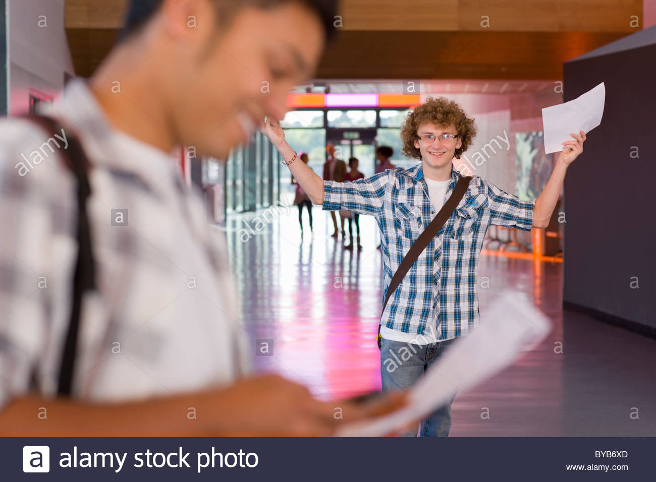 Excited student cheering after receiving good news about test results - Stock Image