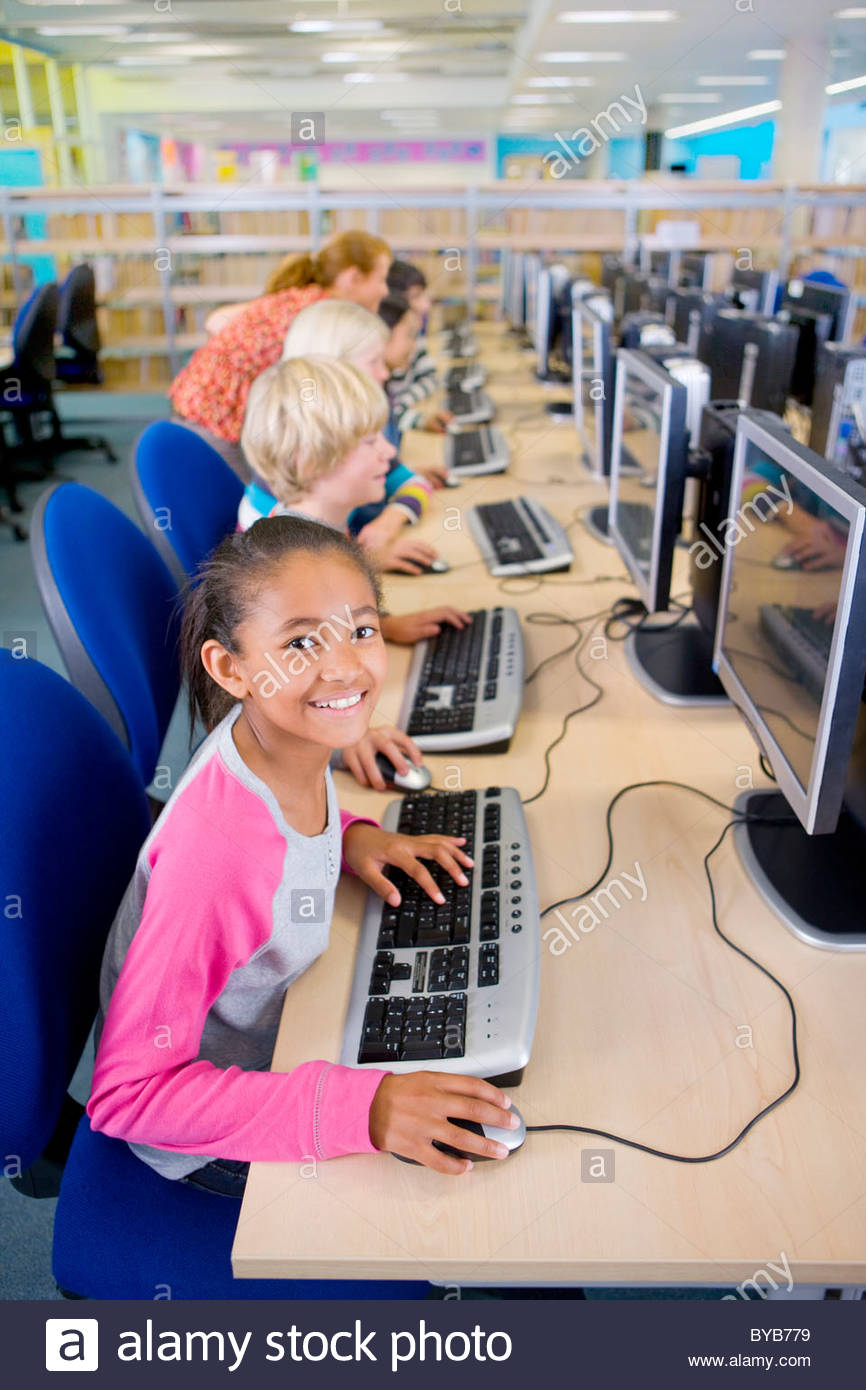 Smiling student using computers in school computer lab - Stock Image