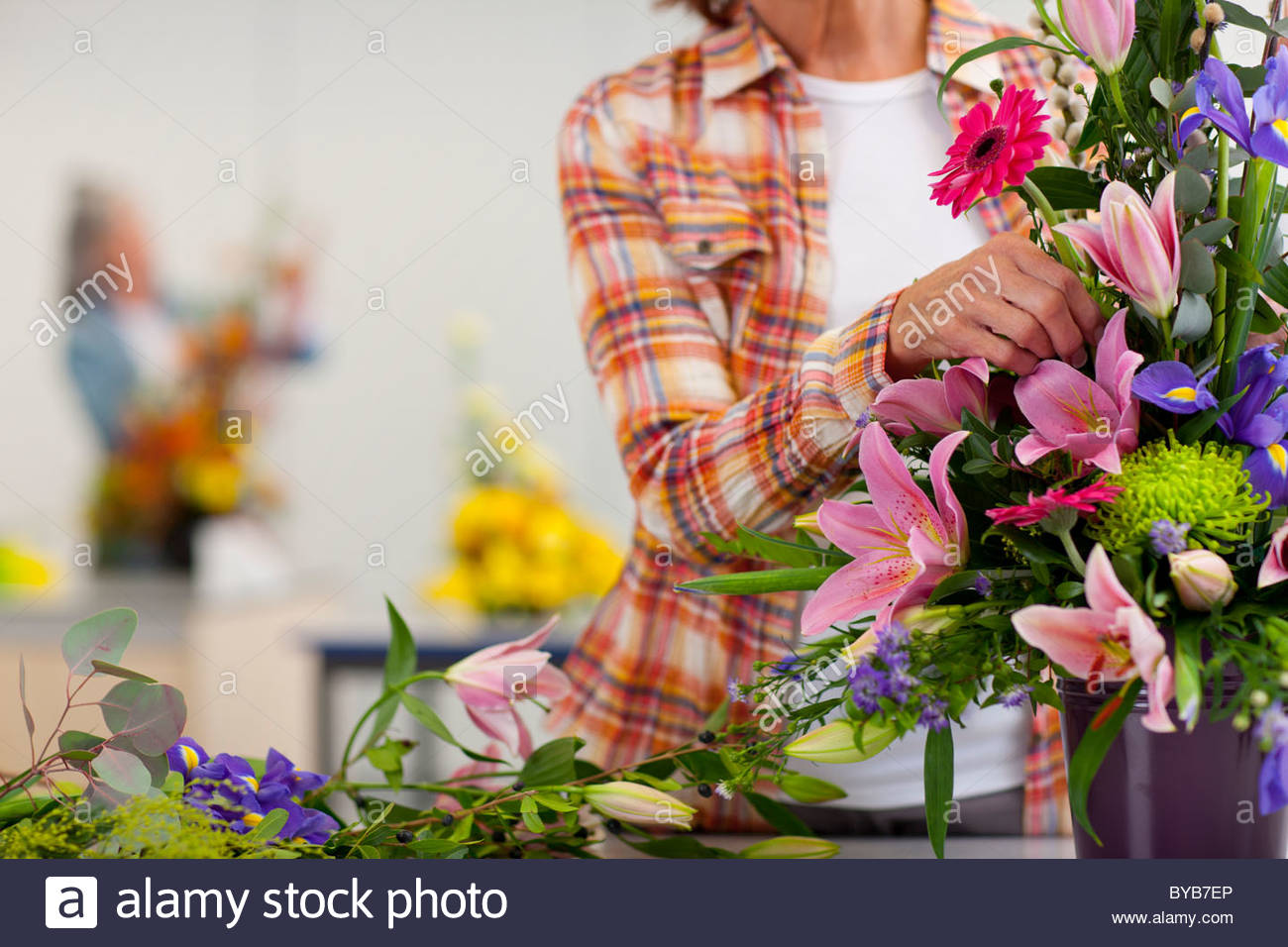 Woman putting flowers into floral arrangement in classroom - Stock Image