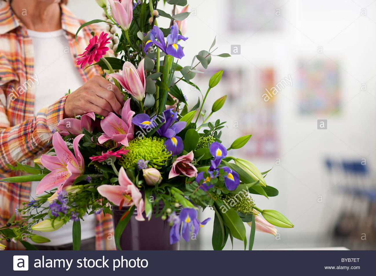 Woman putting flowers into floral arrangement - Stock Image