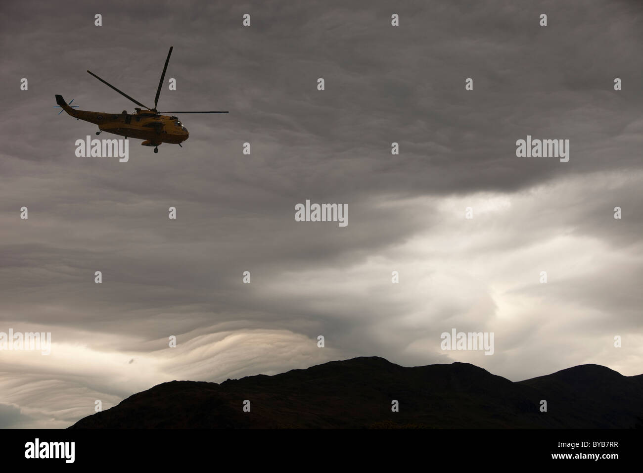 Patterns in cloud on an occluded front over the Lake District hills in Ambleside, Cumbria, UK, with a helicopter. - Stock Image