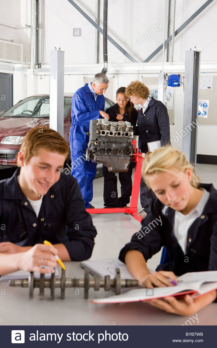 Students with auto part studying automotive trade in vocational school - Stock Image