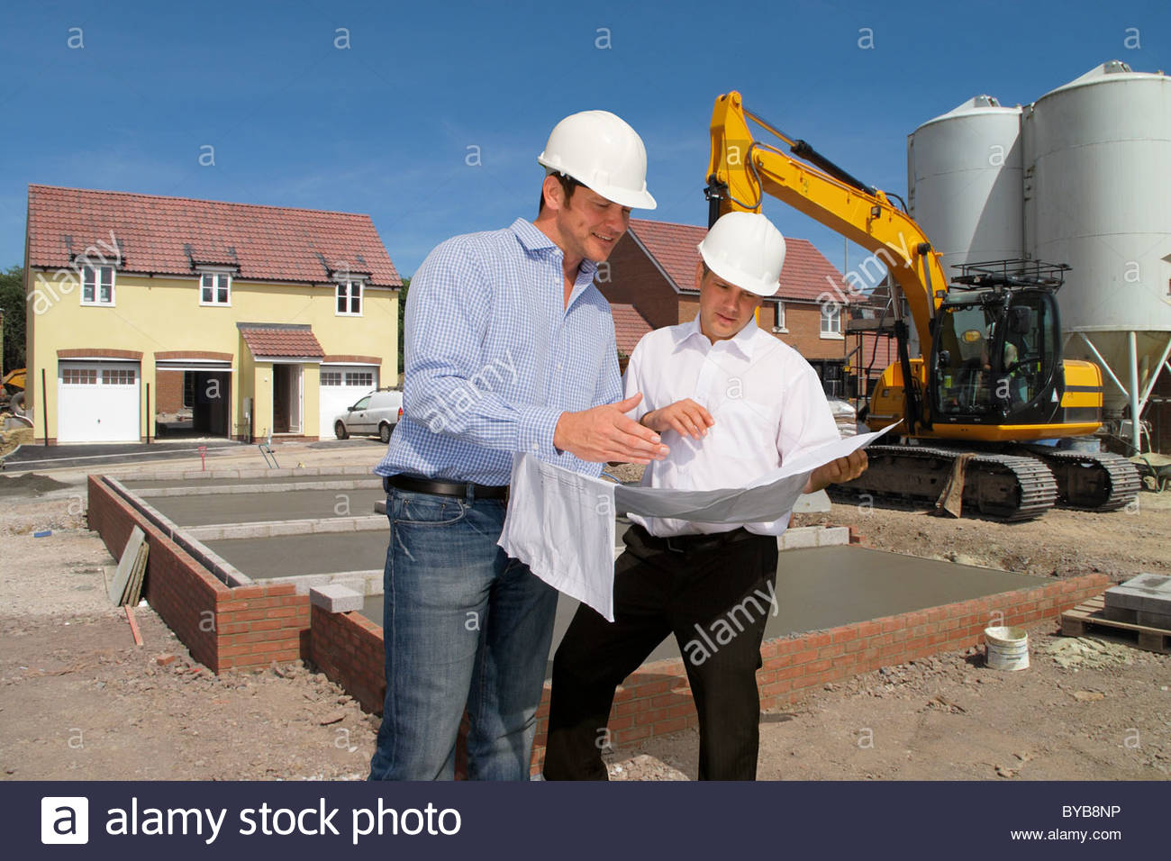 Construction workers holding blueprints talking on construction site Stock Photo