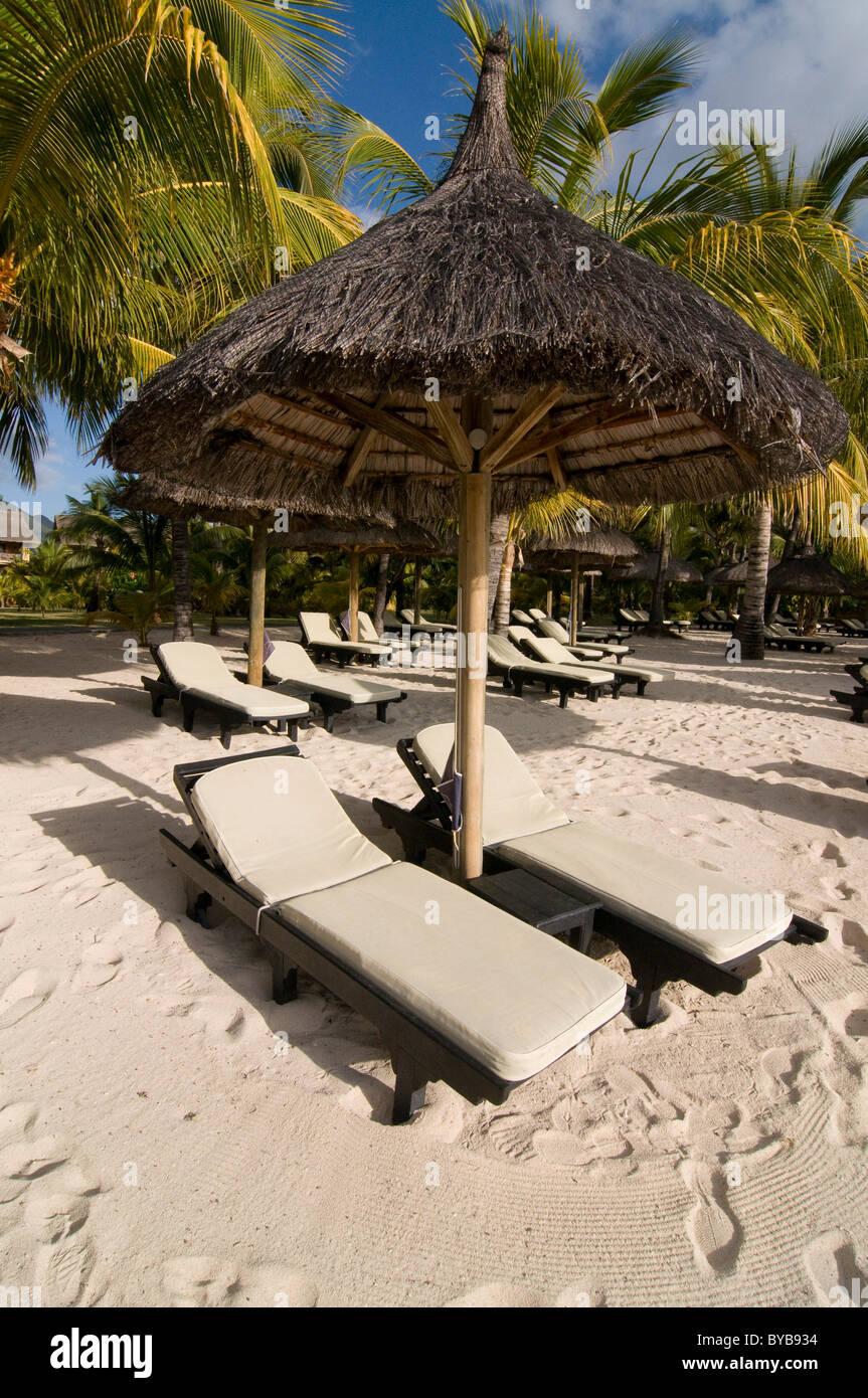 Sunbeds under sunshade on the beach of Le Paradis Hotel, Mauritius, Africa Stock Photo
