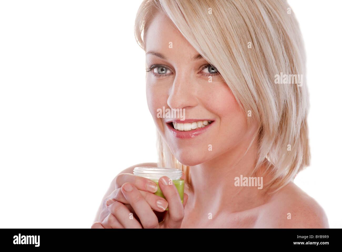 blonde woman holding jar of face cream skincare - Stock Image