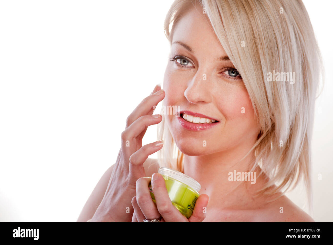 blonde woman applying face cream holding the jar in her hand. - Stock Image