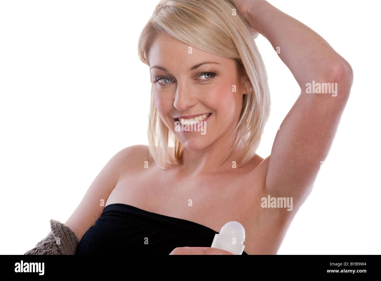 blonde woman applying deodorant to underarms - Stock Image