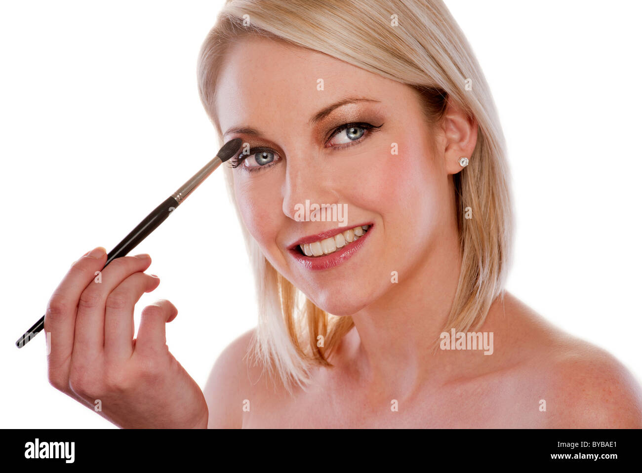 blonde woman applying eyeshadow with a brush - Stock Image