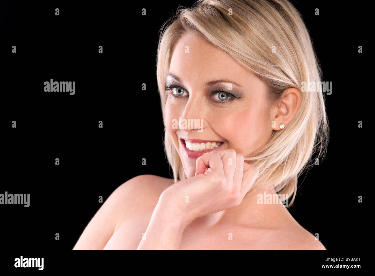 blonde woman smiling with her hand up to her chin - Stock Image