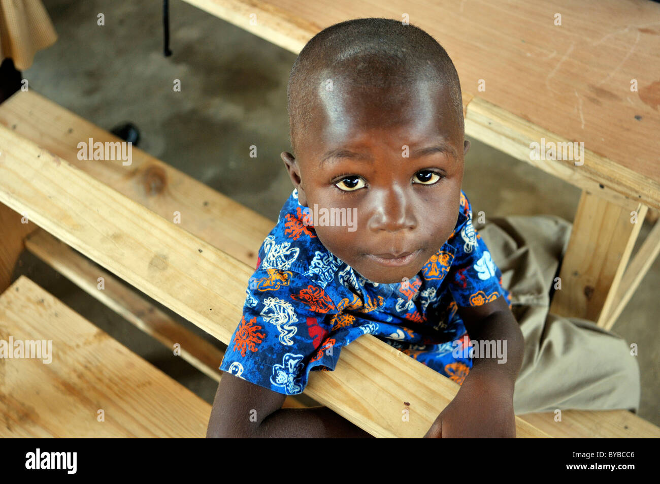Young boy sitting on a school bench in a camp for victims of the January 2010 earthquake, Croix-des-Bouquets district, Stock Photo