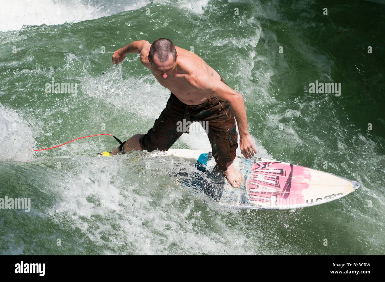 River surfing at Englischer garten in Munich, Germany. - Stock Image