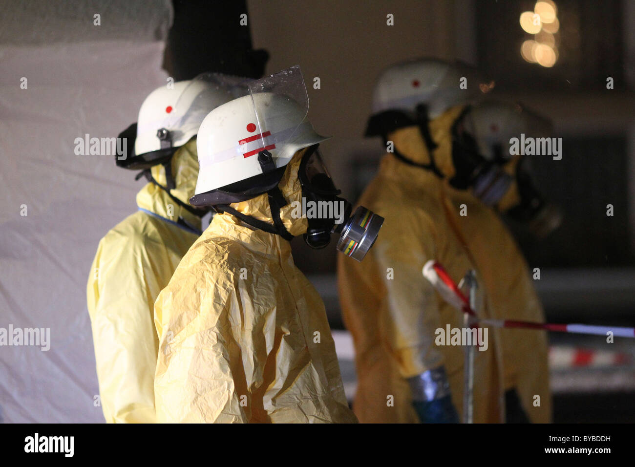 Firefighters equipped for containment of a hazardous substances wearing protective clothing, helmets and respirator - Stock Image