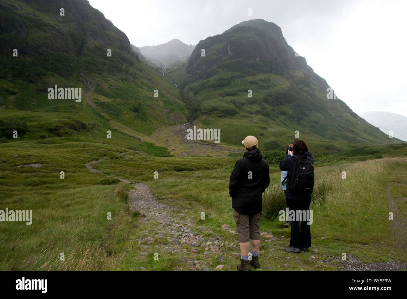 Group of walkers standing on a mountain path looking towards a mountain pass and taking a photo - Stock Image