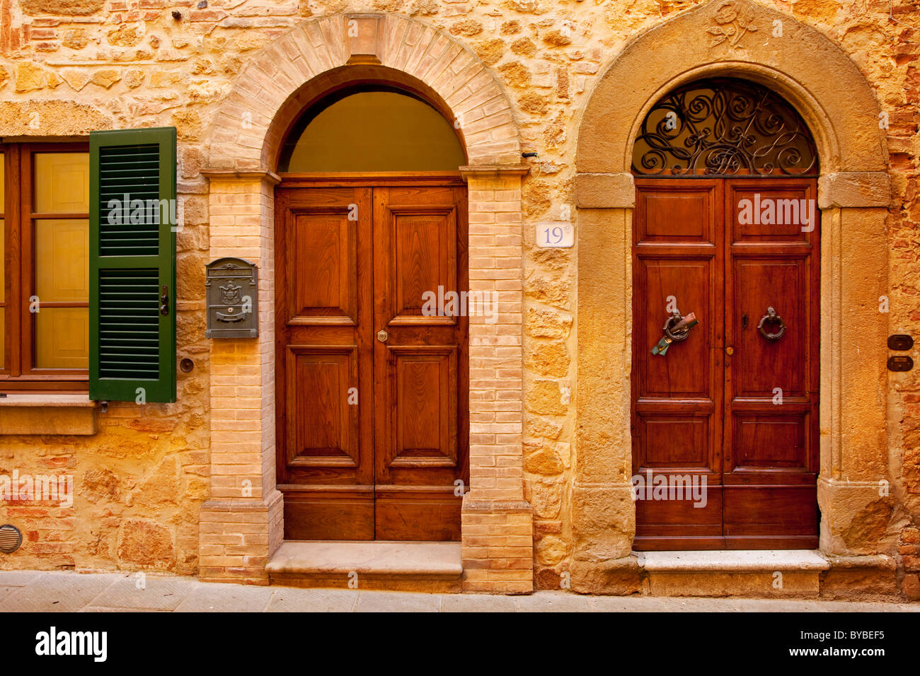 Wooden front doors to homes in medieval village of Castelmuzio near Montisi, Tuscany Italy - Stock Image