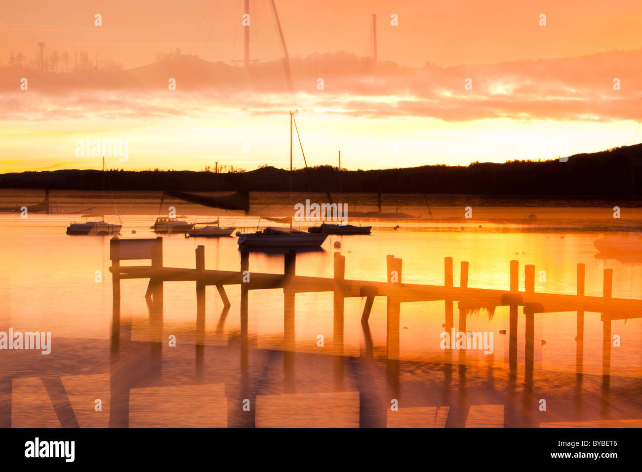 Lake Windermere at sunset with the reflection of a jetty, Lake District, UK. - Stock Image