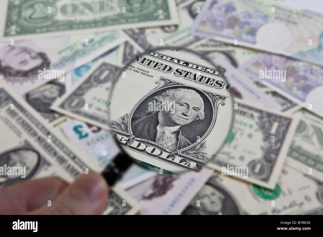 Observation of the U.S. dollar in relation to other currencies with a magnifying glass - Stock Image
