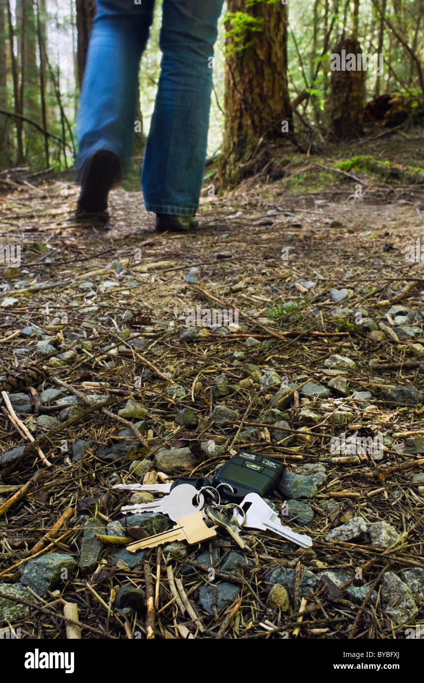A set of house and car keys lay on the forest floor as a person walks away. - Stock Image