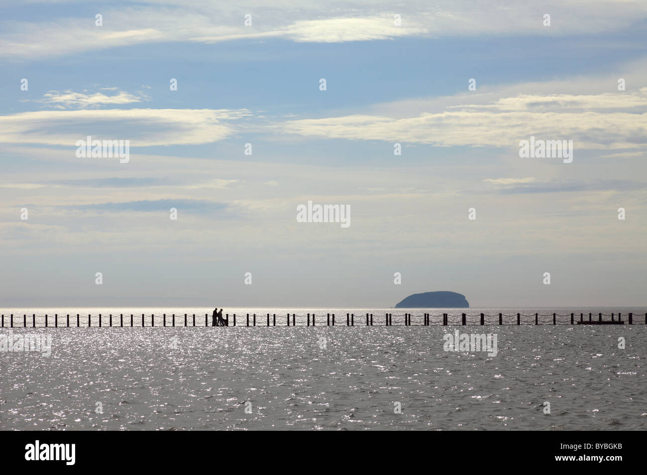 People pushing a wheel chair across the causeway at Marine Lake, Weston Super Mare - Stock Image