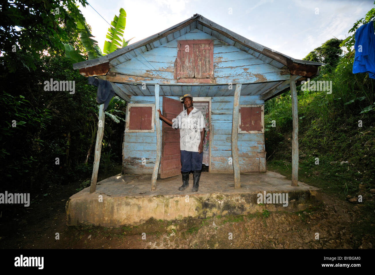Man in front of his traditional wooden house which was badly damaged by the earthquake in January 2010,  village - Stock Image