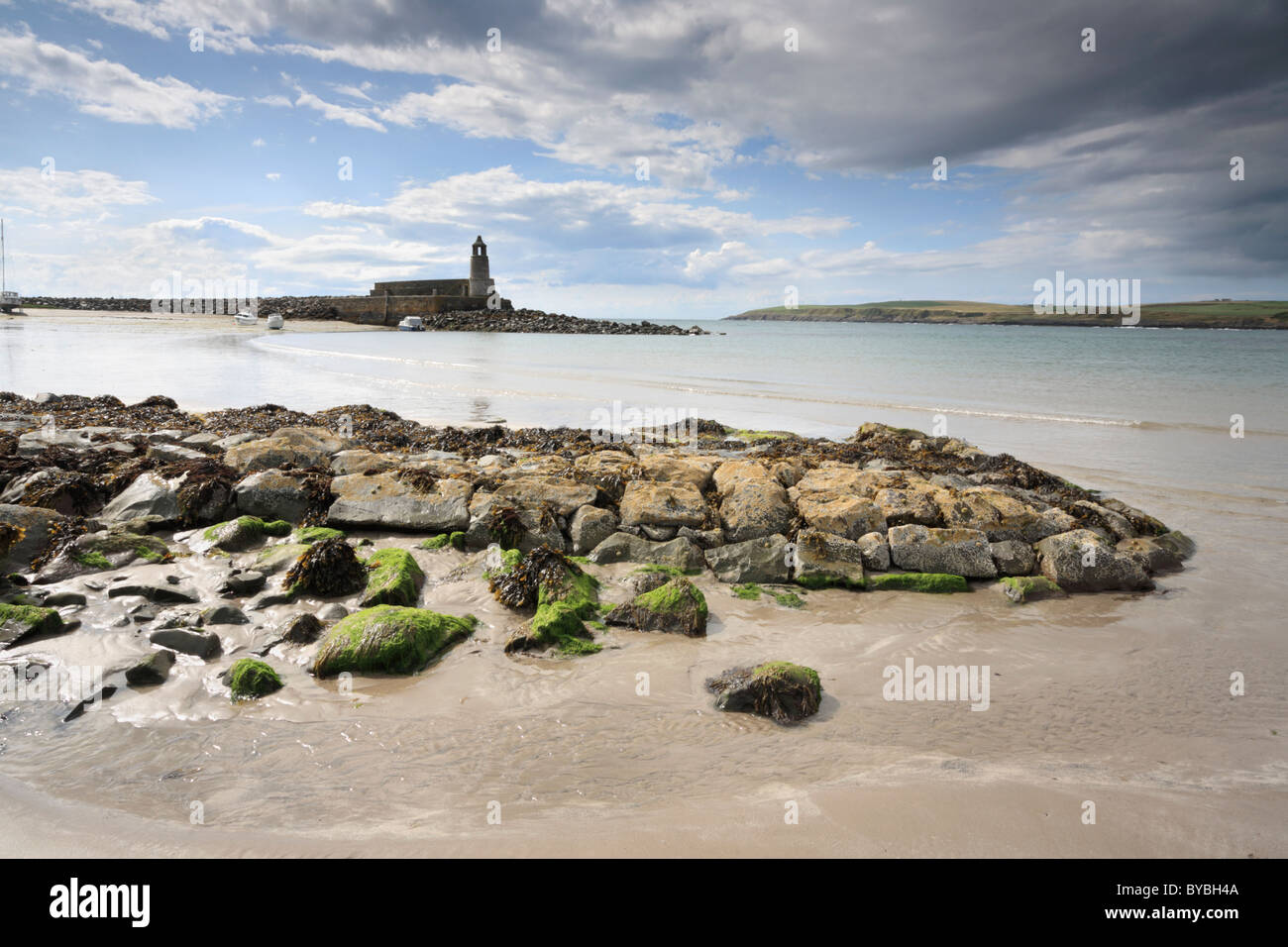 The view across Port Logan beach towards the pier and lighthouse on Scotlands Rhins peninsular - Stock Image