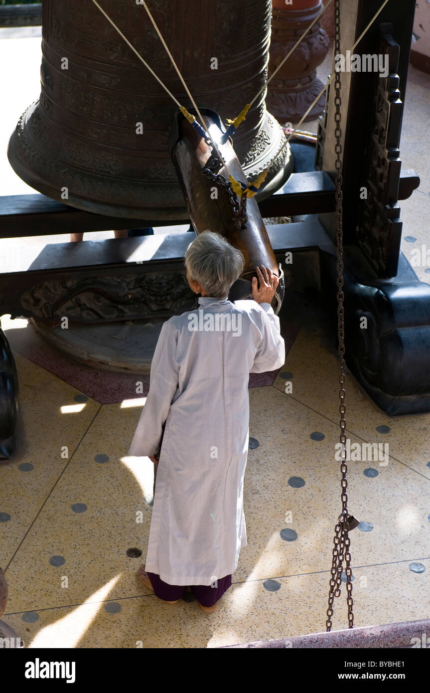 Old man with bell in Long Son Pagoda, Nha Trang, Vietnam, Asia Stock Photo