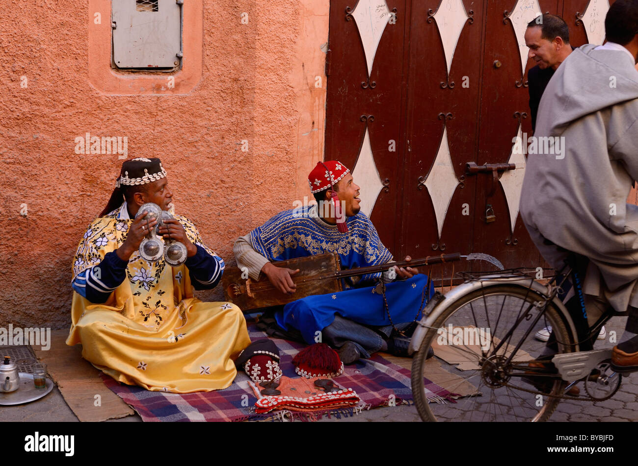 Pair of Gnawa street musicians playing hajhuj and krakeb in Marrakech talking to passerby Morocco - Stock Image