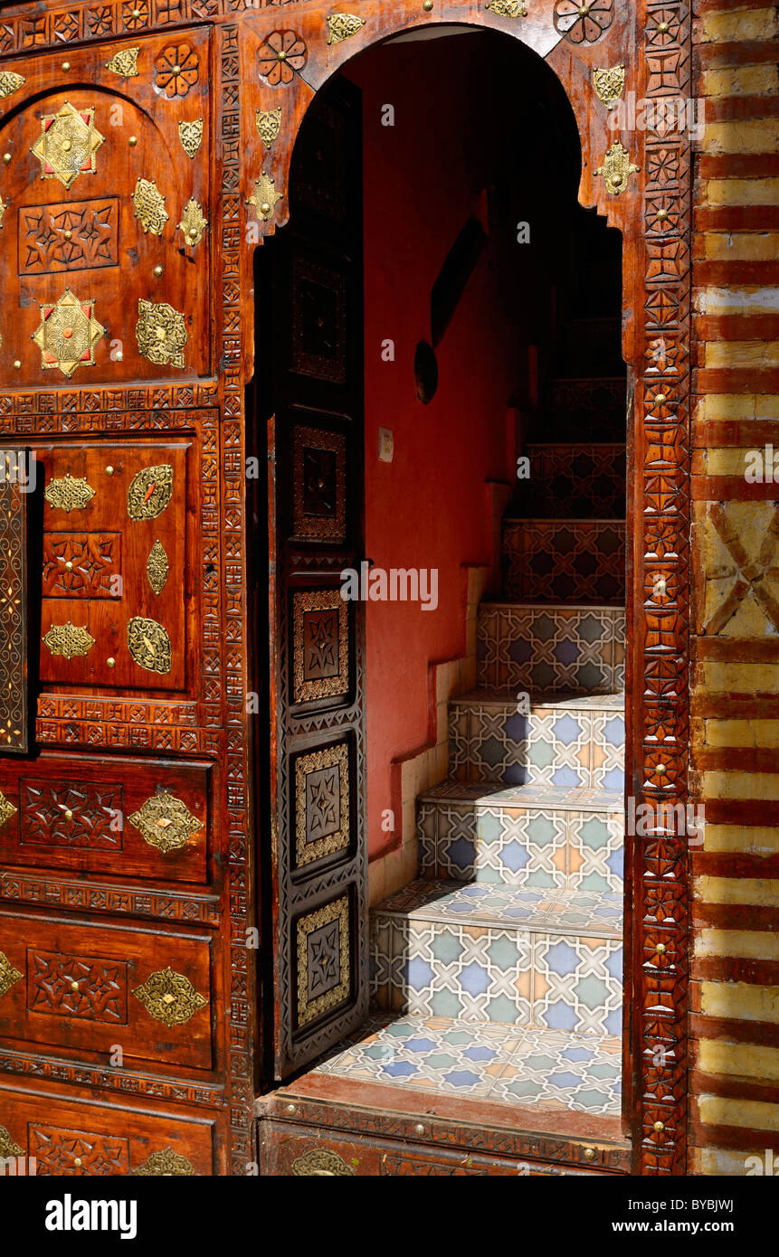 Ornate carved wood and brass door with tile steps in the Marrakesh medina souk Morocco Stock Photo