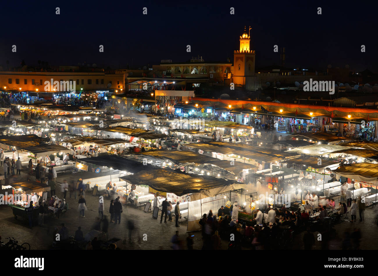 Crowds at the food vendors at night in Place Djemaa el Fna square souk in Marrakech Morocco - Stock Image