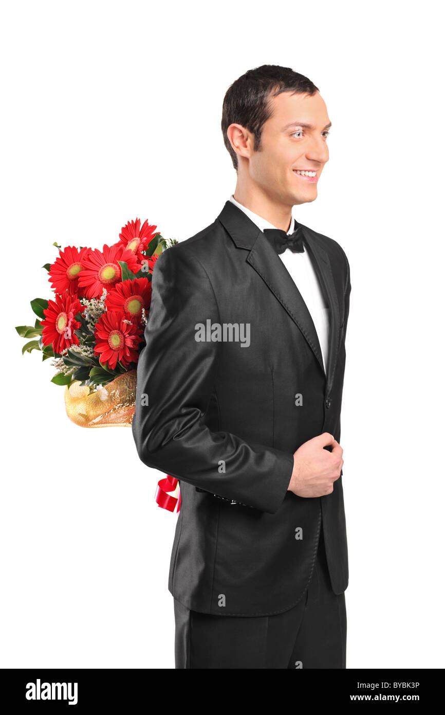 Man wearing suit and bow tie hiding a bouquet of flowers behind his back - Stock Image