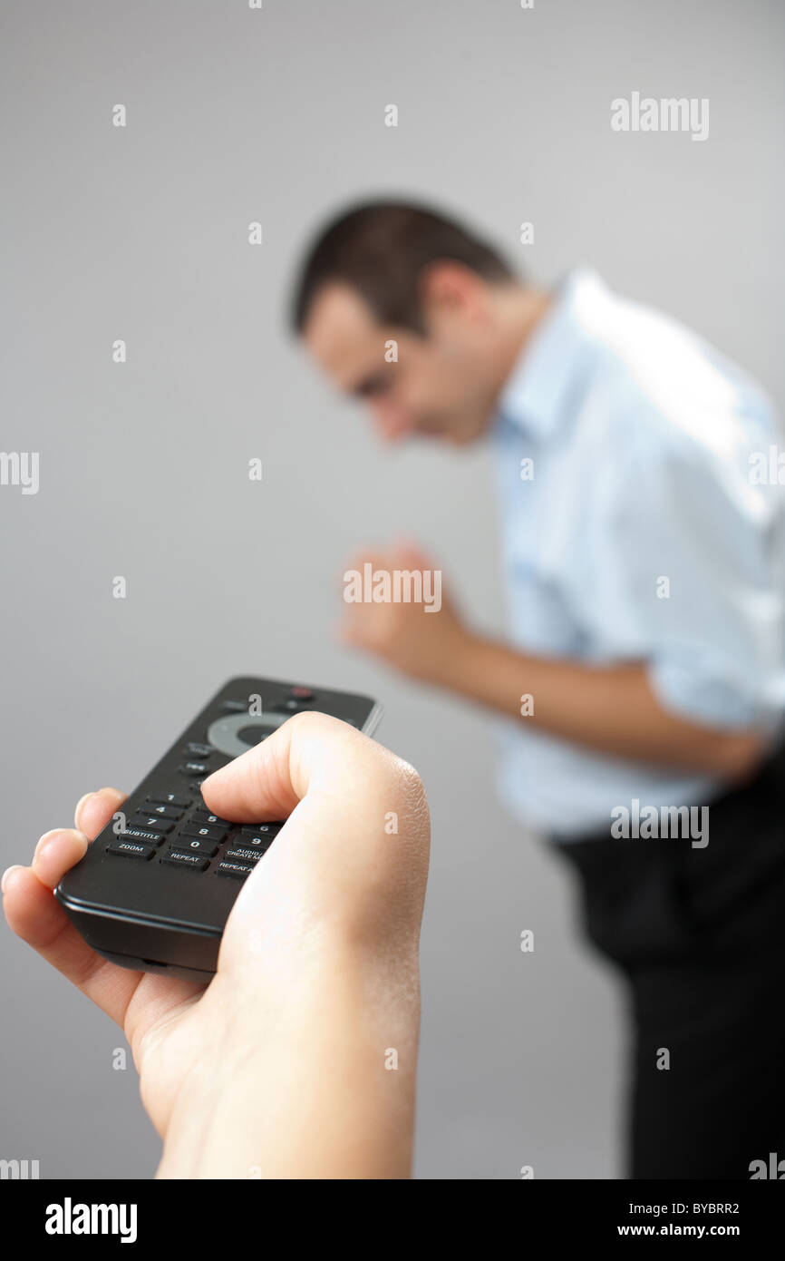Conceptual shot of a man being controlled by his wife with a remote control - Stock Image