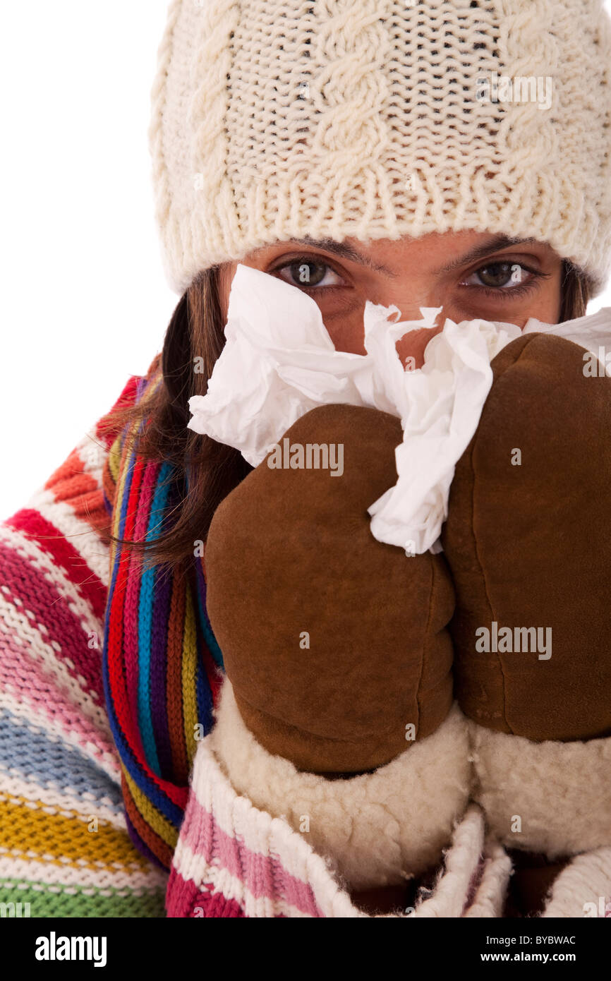 woman sneezing to a paper tissue in winter (isolated on white) - Stock Image