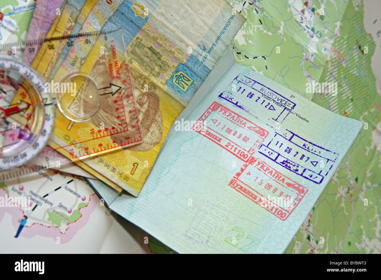 Passport with Ukrainian stamp, banknotes and compass on a map od Ukraine - Stock Image