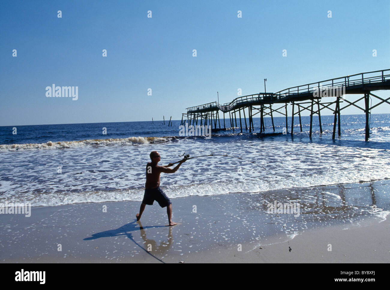 A man surf casts following Hurricane Floyd near a partially destroyed wooden jetty on Oak Island, North Carolina. - Stock Image