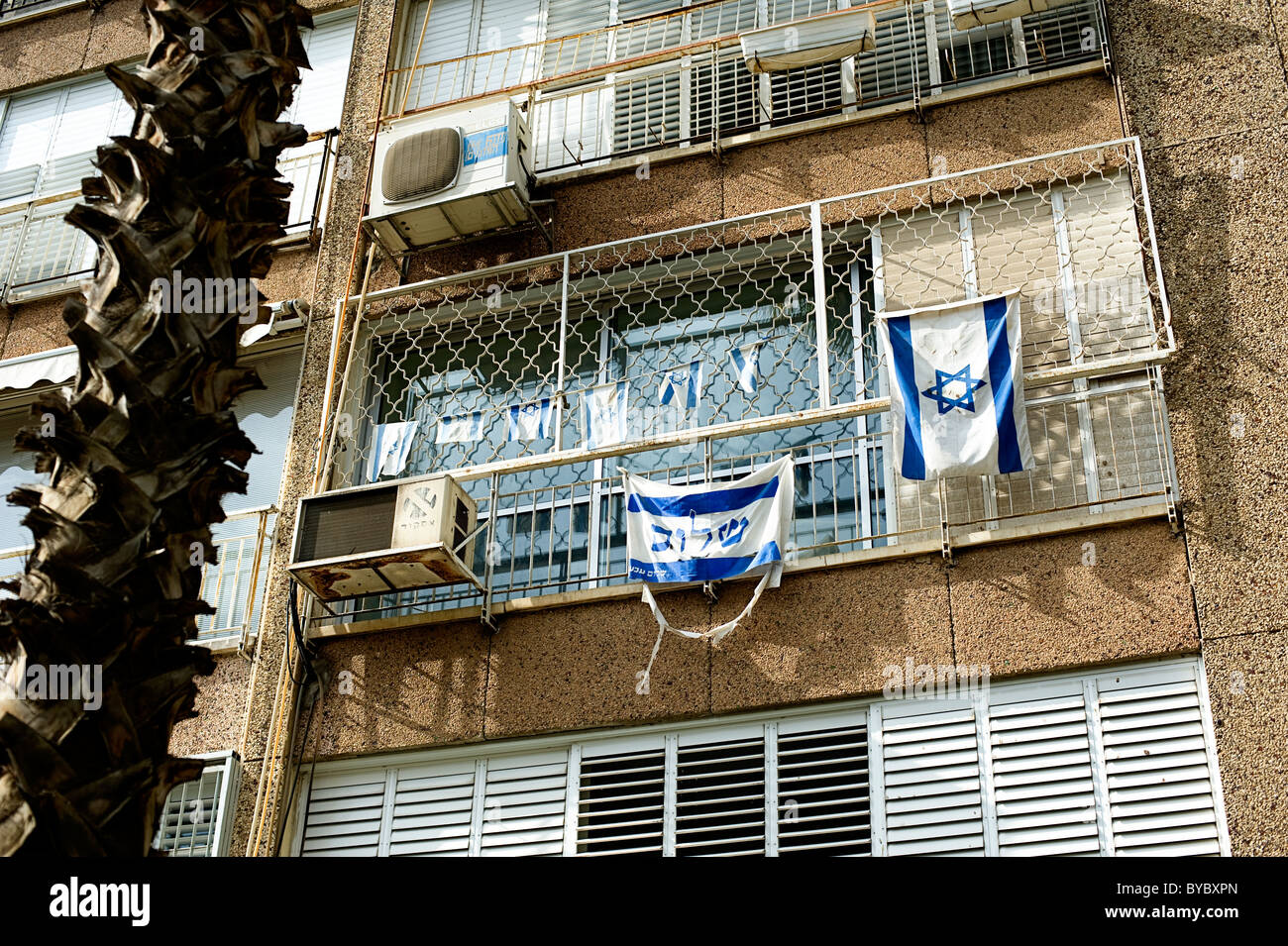 israeli flag and sign saying shalom (peace) in hebrew hanging from the window of a block of flats in tel aviv, israel - Stock Image