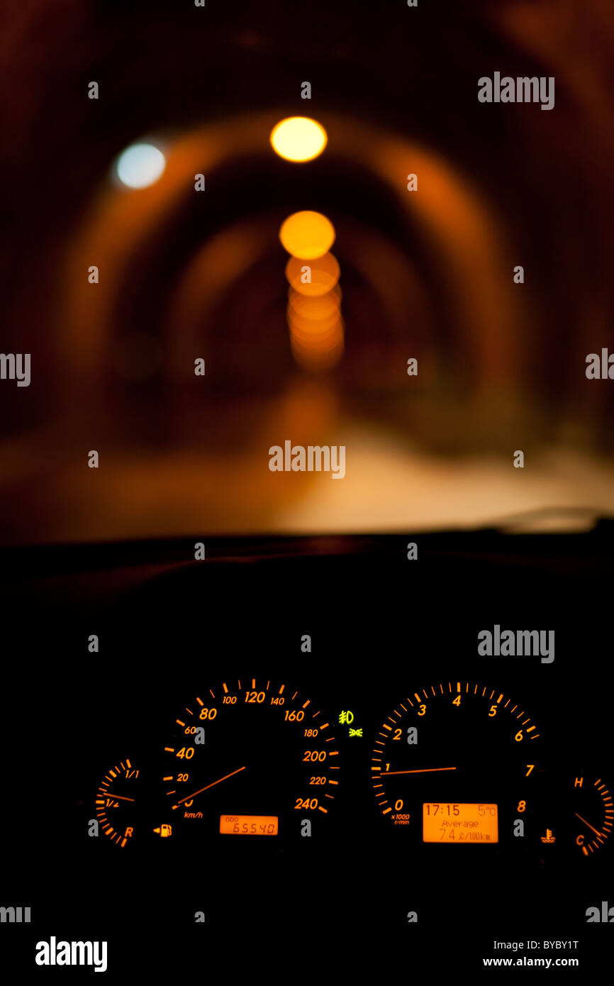 Car dials with a blurred tunnel with lights seen in background - Stock Image