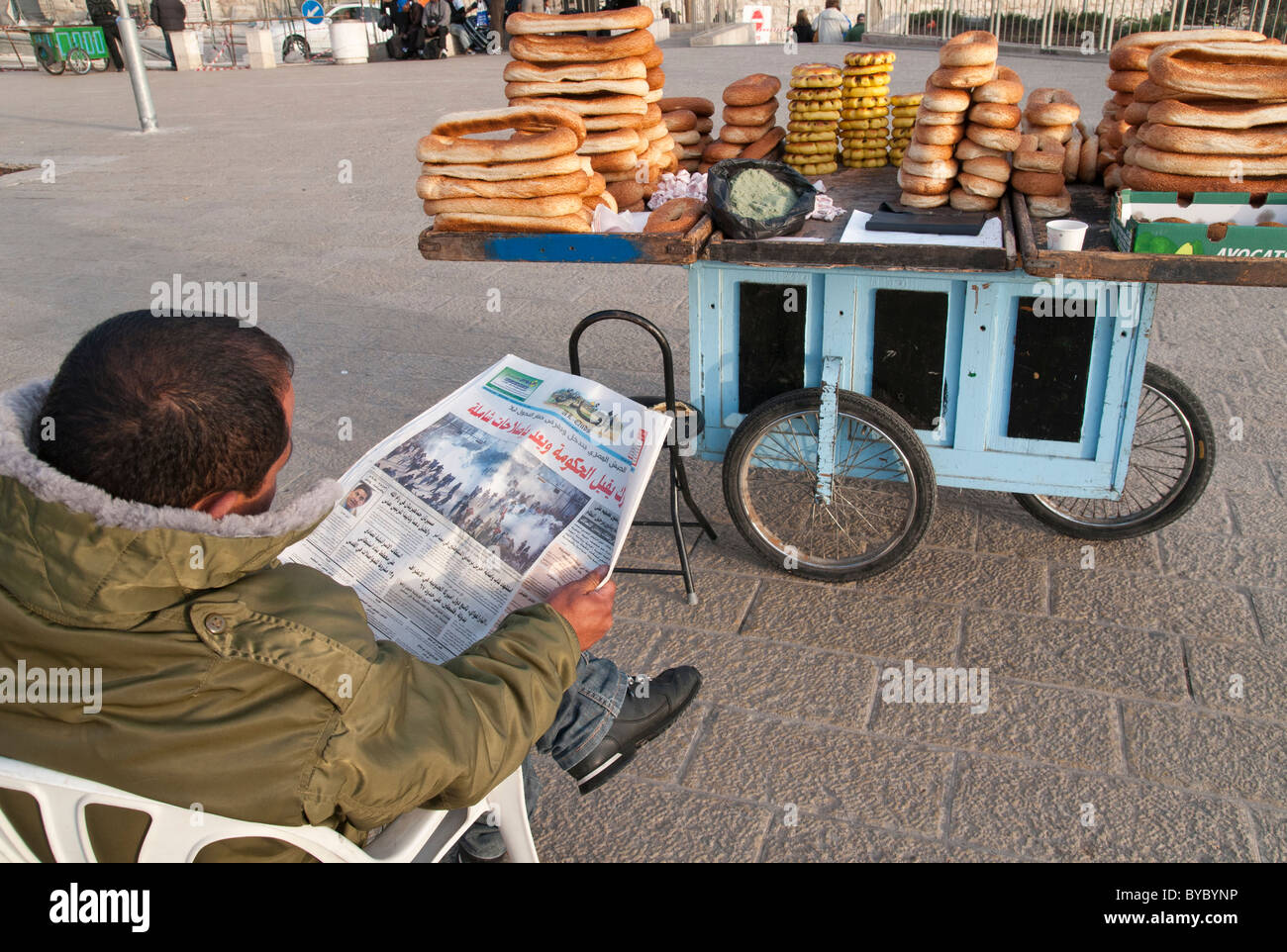 Palestinian hawker reading Al Quds newspaper with picture of protests in Egypt on front page. Jerusalem Old City - Stock Image