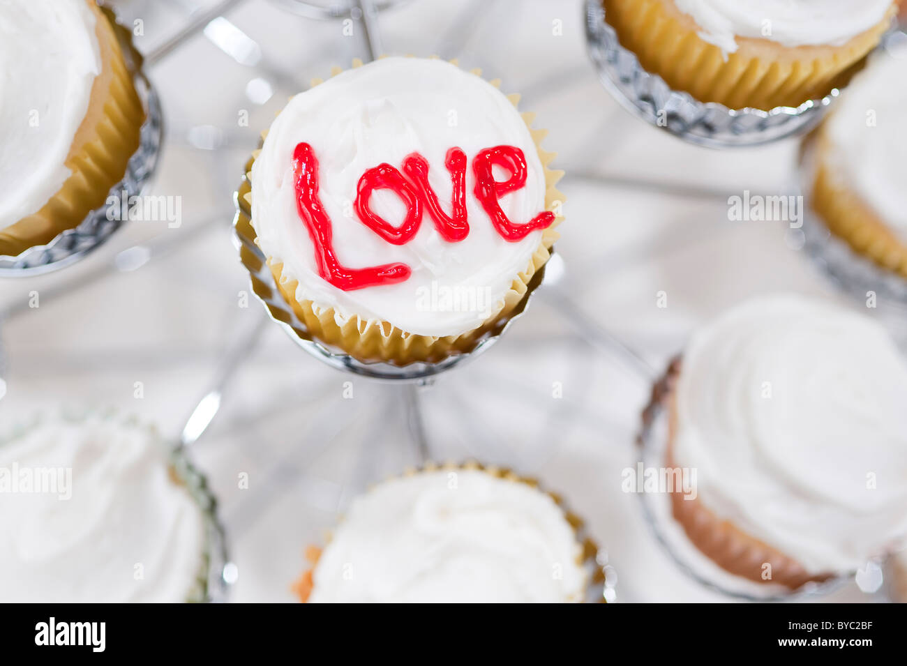 Cupcakes in holder with the letters Love written on top - Stock Image