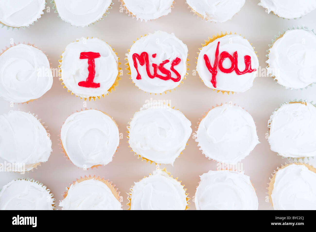 "Rows of cupcakes with red letters ""I Miss You"" written on top of white frosting Stock Photo"