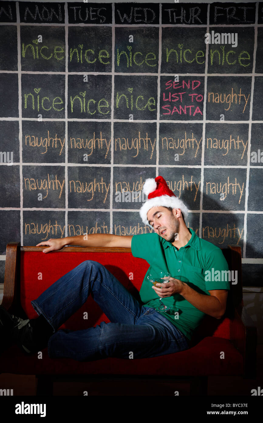 Man with Santa/elf hat and martini alcohol glass in hand asleep in front of Christmas December naughty and nice - Stock Image