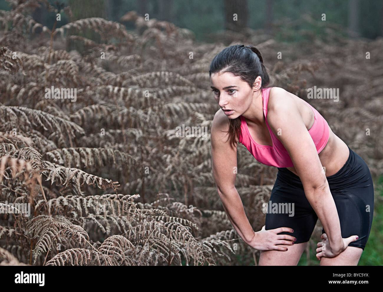 Female taking a breather from a run in the forest - Stock Image