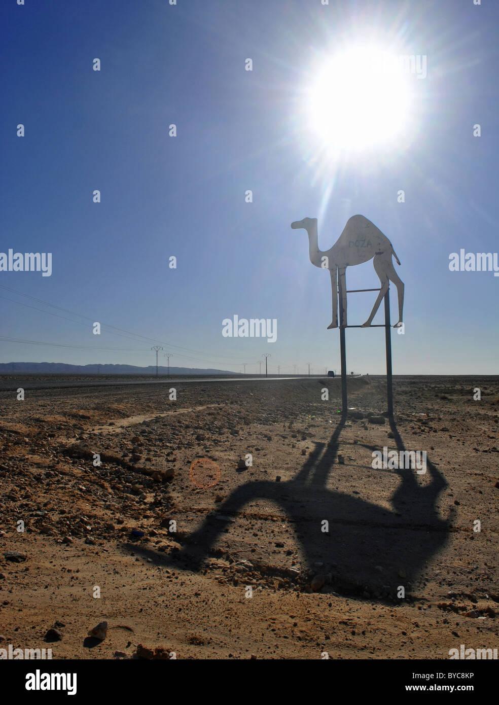 Desert road and camel sign near Douz, Tunisia - Stock Image