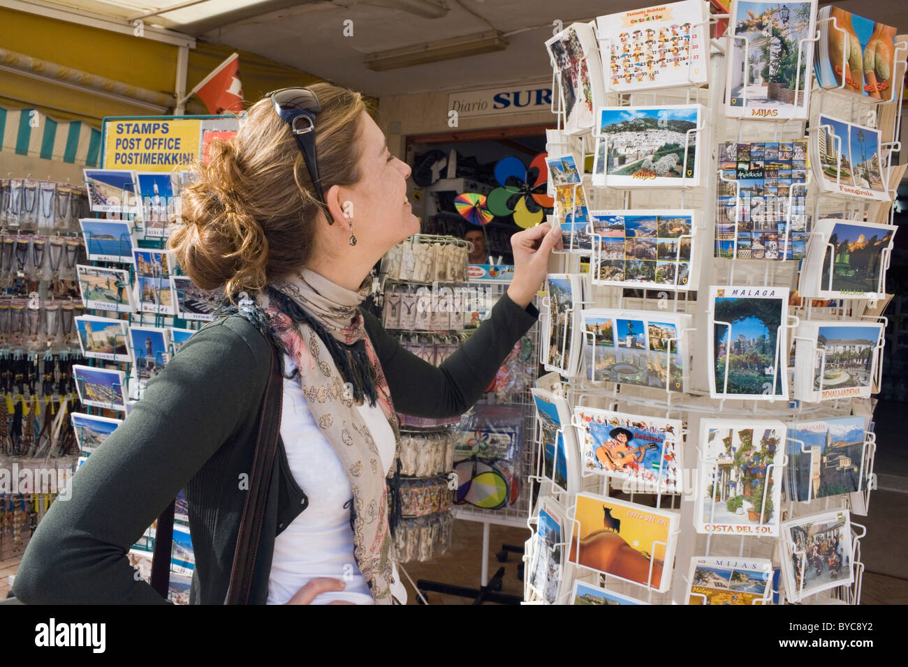 Young woman choosing holiday postcards outside souvenir shop in Los Boliches, Fuengirola, Costa del Sol, Spain. - Stock Image